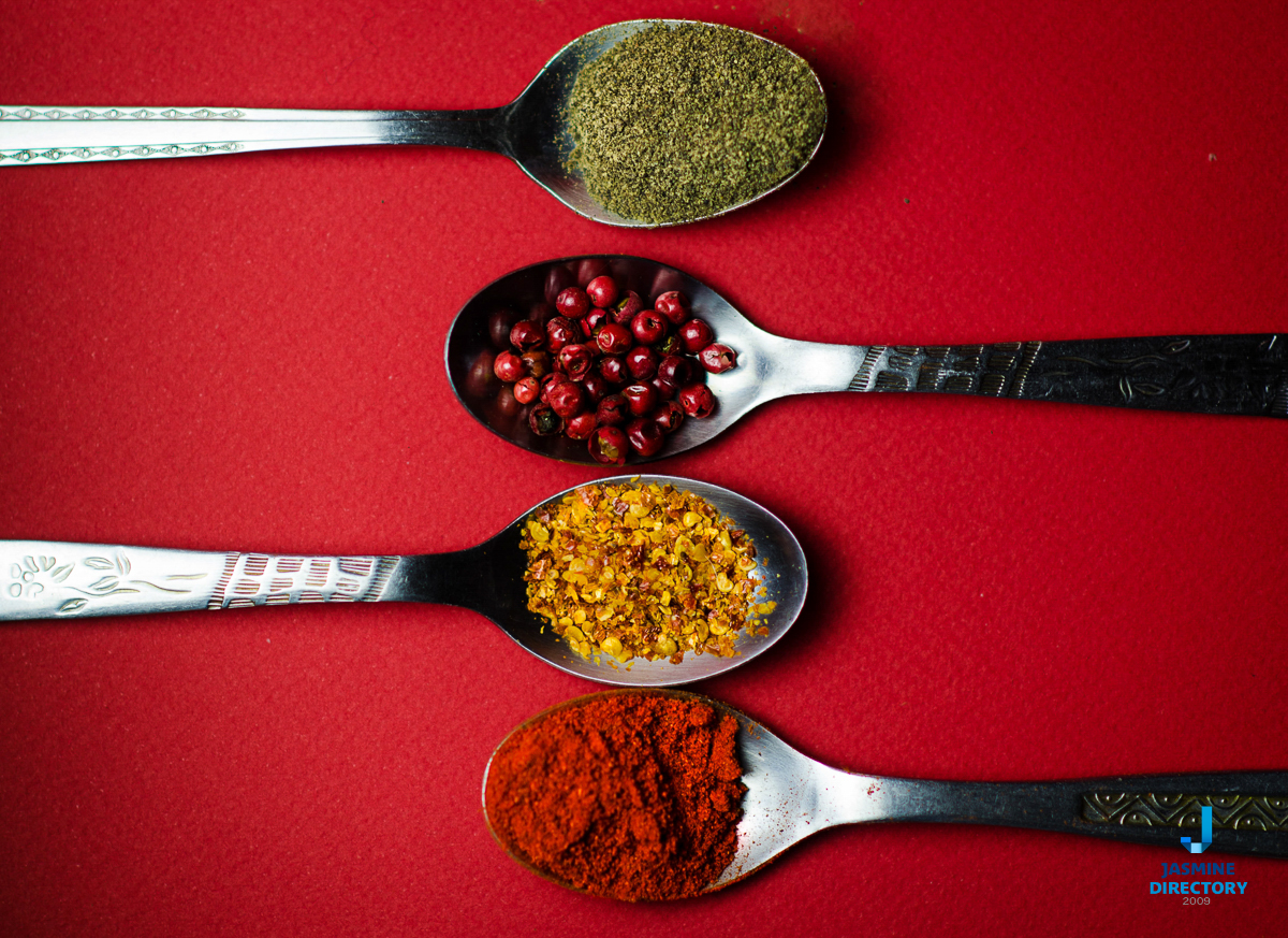 Different spices in spoons and red background